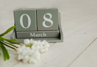 Wooden calendar with 8 March and floowers on white background greeting card