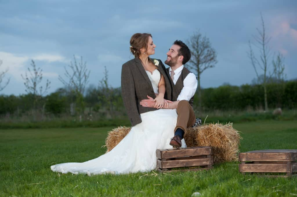 Spring Wedding at South Farm Couple on Hay Bales