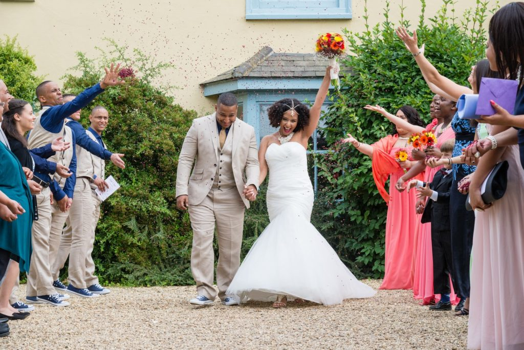 Wedding Couple showered with confetti by their guests at South Farm