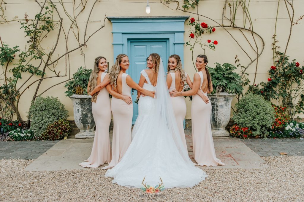 Bride and Bridesmaids smile for photograph in front of Cambridgeshire Wedding Venue