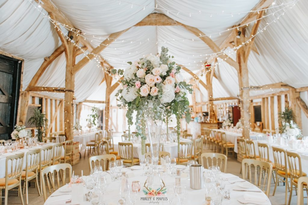 Rustic Barm set for wedding meal with beautiful flowers and fairy lights