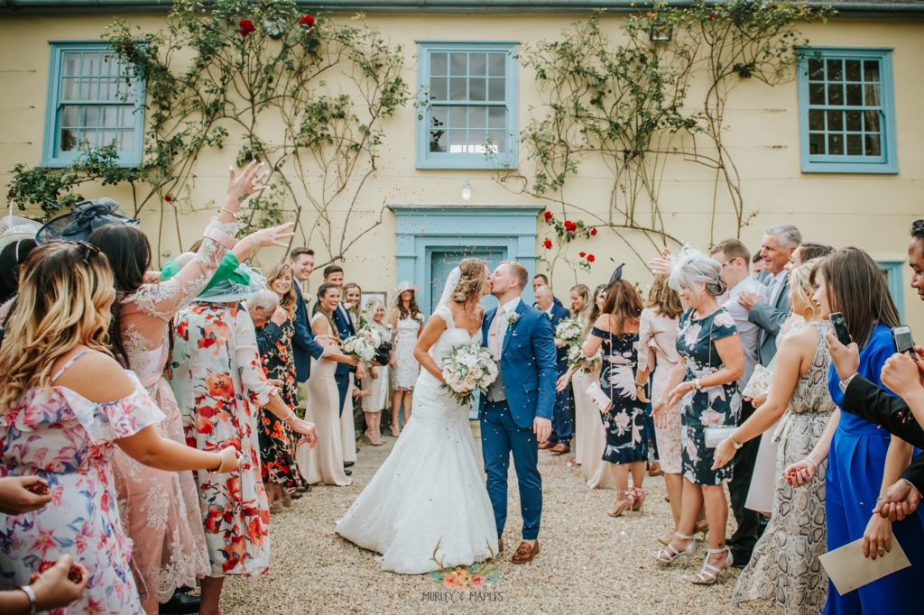 Bride and Groom kiss during confetti shower in front of beautiful country house wedding venue