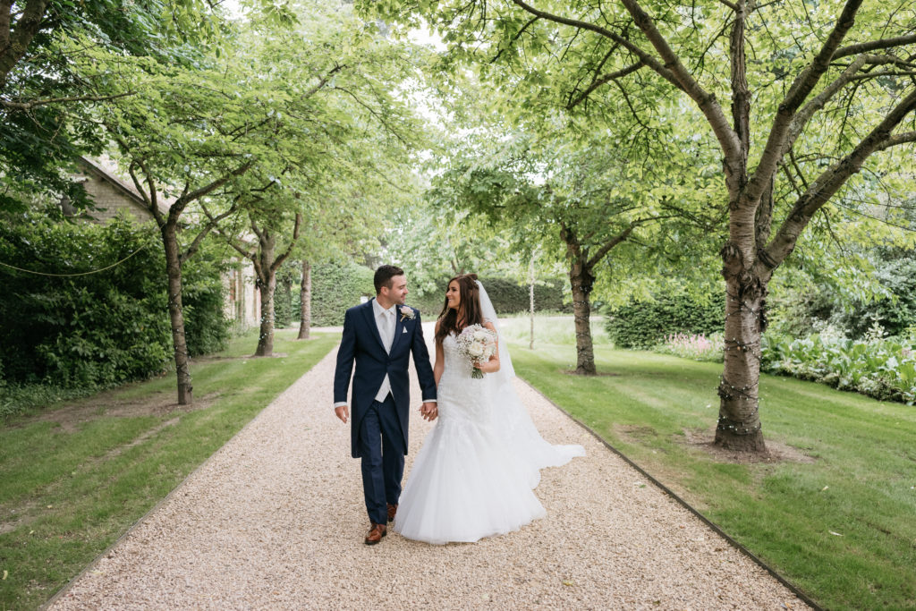 Bride and Groom in tree lined driveway at countryside wedding venue